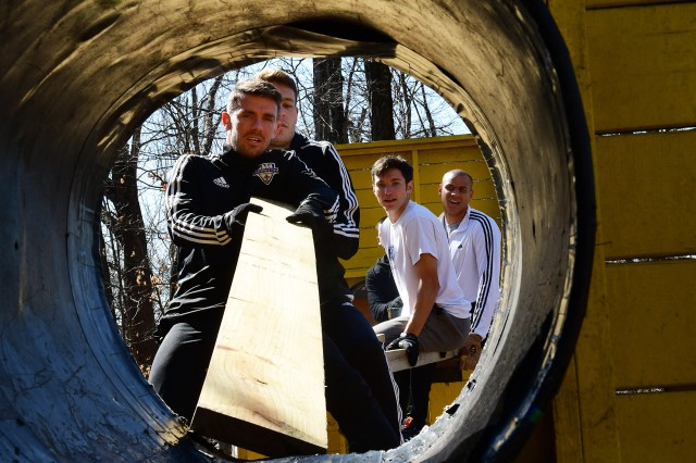 Niall McCabe, midfielder for the USL champion Louisville City FC, struggles to place a board into a culvert at the Dunagan Teamork Development course on Fort Knox Tuesday as fellow midfielder Magnus Rasmussen attempts to help. Several members of the team visited the post all day to meet Soldiers and Families as well as to develop some teamwork and leadership skills.