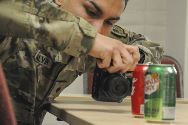 Spc. Johnathan Galvin, military police investigator with the 137th Military Police Detachment, photographs evidence during a training event at the Henderson Armory March 4, 2018. Military police investigators perform work equivalent to civilian police detectives.