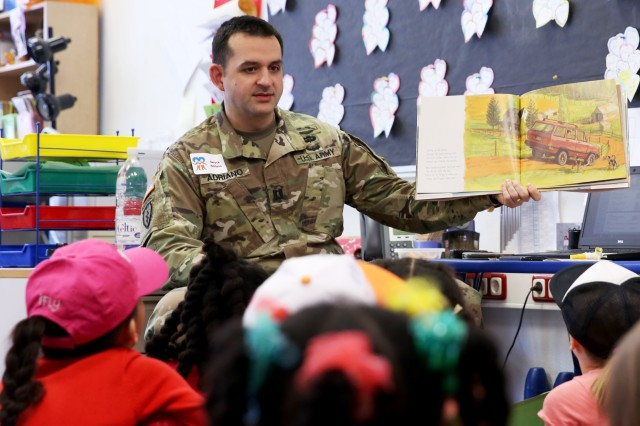 U.S. Army Cpt. Deryck Adriano, Headquarters and Headquarters Company Commander assigned to the Joint Multinational Readiness Center, reads to children during the Read Across America Day reading event at the Hohenfels Elementary School, Hohenfels, Germany, Mar. 2, 2018.