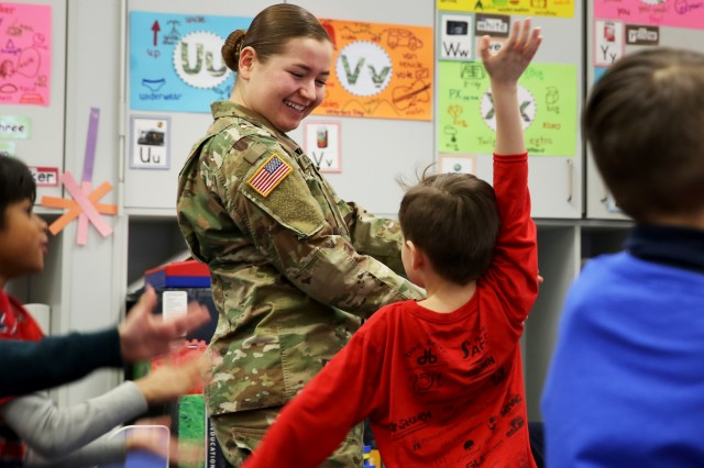 "U.S. Army Pfc. Meagan Mooney, a combat documentation/production specialist assigned to JMRC, dances with kindergarten children during their ""Brain Break"" following the three books she read to them for her reading session during the Read Across America Day reading event at the Hohenfels Elementary School, Hohenfels, Germany, Mar. 2, 2018."