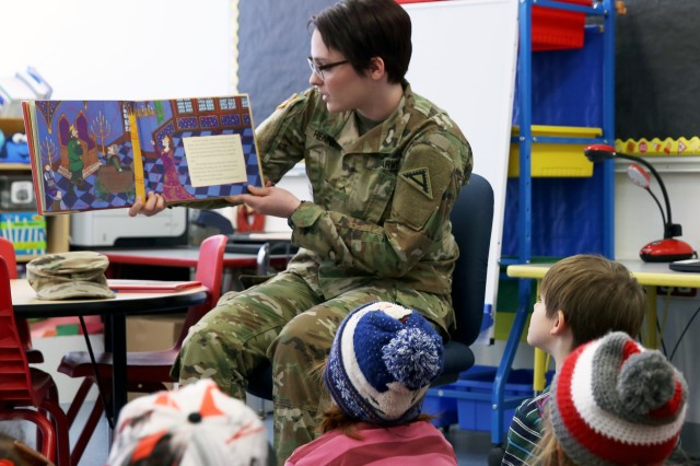 "U.S. Army Pvt. Mikayla Henning, a combat documentation/production specialist assigned to JMRC, reads ""The Red Thread"" to school children for her reading session during the Read Across America Day reading event at the Hohenfels Elementary School, Hohenfels, Germany, Mar. 2, 2018."