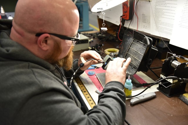 Electronics Technician Steven Tito assembles the connector of a radio interoperability component at Tobyhanna Army Depot.