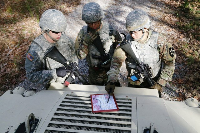 Second Lts. Chris Ashwood, Jinwei Hu, and Kyoohyun Sim look over their map before moving on to the next portion of their mission during the final field training exercise of the Quartermaster Basic Officer Leader Course at Fort Lee, Va., on Nov. 21, 2017.