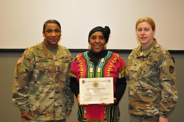 Shellie Moore-Guy receives certificate of appreciation presented by Brig. Gen. Heidi Hoyle and Command Sgt. Maj. Tomeka O'Neal.  (Photo Credit: Eldria Coleman, JMC Public and Congressional Affairs.)
