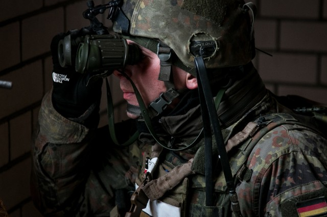 A German soldier assigned to the 1st Mechanized Infantry Company, Enhanced Forward Presence Battle Group Lithuania, looks out a window opening for potential enemies during a multinational rapid response exercise simulated training event with U.S. Soldiers Dec. 14, 2017, near Baltadvaris, Lithuania. The rapid response exercise enhances the United States' abilities to conduct training operations in cooperation with our NATO allies and partners.  (U.S. Army photo by Spc. Dustin D. Biven / 22nd Mobile Public Affairs Detachment)