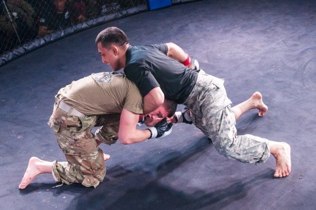 A Soldier with 10th Special Forces Group Airborne and Spc. Brandon Robinson from the 82nd Airborne Division compete in the Lightweight Championship bout during the Annual Fort Bragg Combatives Tournament at Fort Bragg, N.C. March 3, 2018. (U.S. Army photo by Staff Sgt. Jazmin Jenkins/ 22nd Mobile Public Affairs Detachment)
