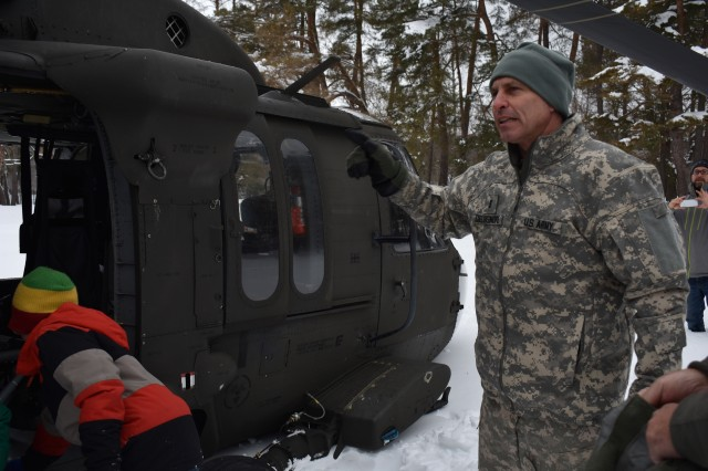 N.Y. Army National Guard Chief Warrant Officer 3 John Delsignore, assigned to 3rd Battalion, 142nd Aviation, talks to local families about the UH-60 Black Hawk, and what his unit does, in Cooperstown, N.Y., March 3rd, 2018. Unit members were conducting a training exercise with an Army Reserve Civil Affairs company and local residents had gathered to see the helicopters. Delsignore talked to the family about how the National Guard helps the community by reacting to state emergencies, and providing support to other units while deployed.