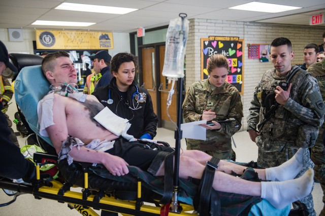 Sgt. Kevin Lovelace, right, alerts a local hospital via radio of an inbound patient during a March 4, 2018, medical training exercise in Waukesha, Wis. Combat medics from the 135th Area Support Medical Company, Wisconsin Army National Guard, partnered with local first responders from multiple agencies to exchange tactics, techniques, and procedures in a mass casualty situation.