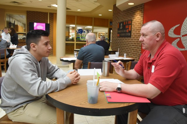 Robert Byrd (right), chief of the Command Initiatives Group at McAlester Army Ammunition Plant, Okla., talks to Noah Thomas, a student at Kiamichi Technology Center in McAlester, Okla., on Feb. 27. Byrd was a representative from one of the 30 businesses in the McAlester area that KTC invited to participate in its Mock Interview Day for its students.