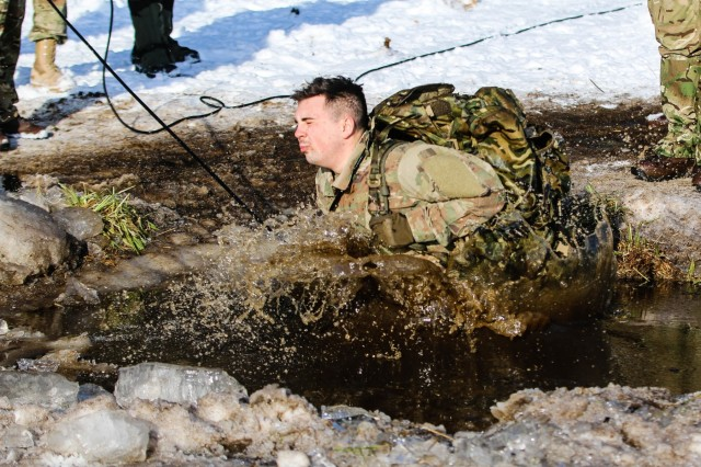 Pfc. Ryan Oliver, a Denver, Colorado native and a wheeled vehicle mechanic with the 82nd Brigade Engineer Battalion, 2nd Armored Brigade Combat Team, 1st Infantry Division, jumps into a lake during cold-water immersion training with the U.K. 1st Royal Welsh Battalion in Tapa, Estonia on March 7, 2018 as part of an rapid response readiness exercise in support of Atlantic Resolve. The 2nd ABCT demonstrates readiness by training and exercising it's ability to quickly mass, mobilize and perform it's warfighting functions with NATO allies and by building and displaying maximum proficiency in its capabilities. (U.S. Army photo by Spc. Hubert D. Delany III/22nd Mobile Public Affairs Detachment)