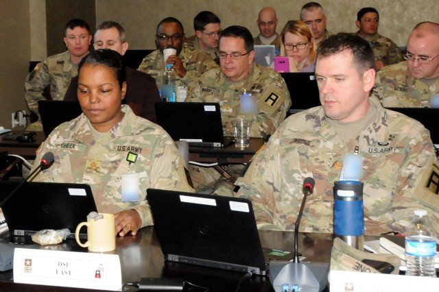 Maj. Mikhaela Cheek (left) of the First Army Division East G3 directorate, and Maj. Bob   Stone of the 157th Infantry Brigade take notes during the First Army Training Support and Synchronization Working Group on March 6 in the Pershing Conference Room of First Army headquarters on Rock Island Arsenal, Ill.