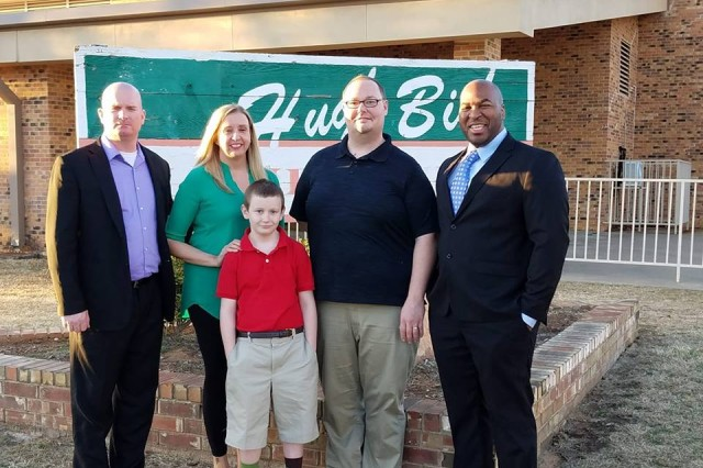 Sgt. 1st Class Michael McGill Jr. (left) and other members of the School of Athens board stand in front of Hugh Bish Elementary School in Lawton. McGill's son Michael III (center), age 9, proposed the idea of a fundraiser when he learned some of his classmates were going hungry.
