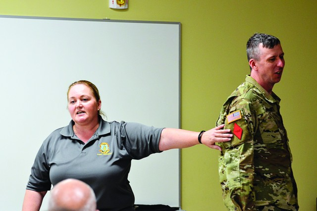 Mary Reardon, safety specialist with the Fort Jackson Safety Office places the red heat patch on 1st Sgt. Jerod Burghardt to demonstrate the location of the patch, to identify Soldiers who have had prior heat illness during the 1st Battalion, 13th Infantry Regiment Heat Illness Prevention Training.