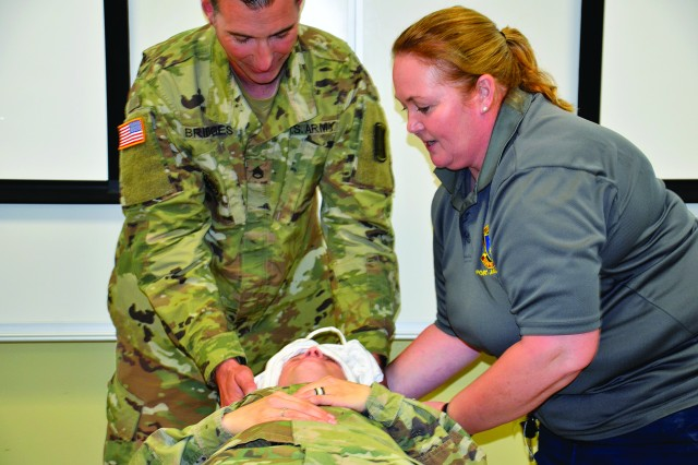 Mary Reardon, a safety specialist with the Fort Jackson Safety Office, demonstrates how to effectively apply an ice sheet March 2 during Heat Illness Preventing training for 1st Battalion, 13th Infantry Regiment. Staff Sgt. Michael Bridges, left, assists in the ice sheet demonstration by first wrapping Staff Sgt. Aryanna Phillips' head with an ice sheet before moving on to apply ice sheets to the rest of her body.