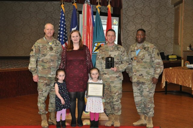 The Berta Family poses with Maj. Gen. Pete Johnson, post commander, and Command Sgt. Maj. Lamont Christian, post senior enlisted leader, after being named Family of the Year.