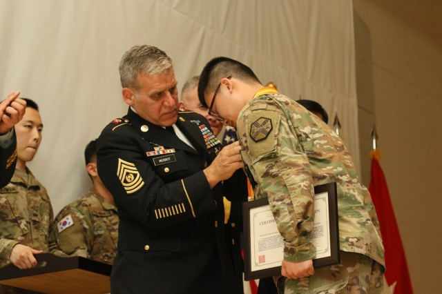 Command Sgt. Maj. Richard Merritt, Eighth Army command sergeant major, presents a Best KATUSA Award to Sgt. Kim, Kang. Kim is the senior KATUSA for Headquarters and Headquarters Company, U.S. Army Garrison Humphreys.
