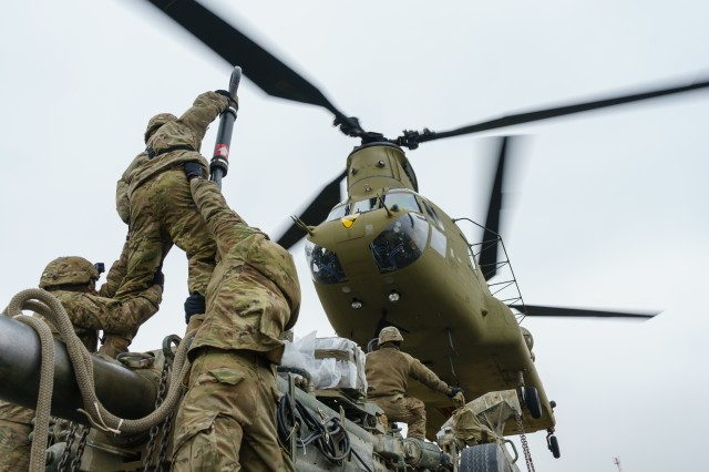 A CH-47 Chinook helicopter crew assigned to Company B, 2nd General Support Aviation Battalion, 227th Aviation Regiment, 1st Combat Aviation Brigade, 1st Cavalry Division, moves into position over artillerymen with Battery B, Field Artillery Squadron, 2nd Cavalry Regiment, to sling load an M777 howitzer during training at an airfield near Grafenwoehr, Germany Mar. 6, 2018.