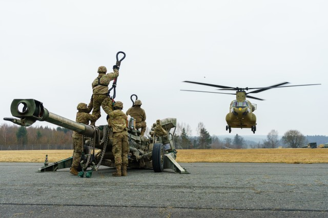A CH-47 Chinook helicopter crew assigned to Company B, 2nd General Support Aviation Battalion, 227th Aviation Regiment, 1st Combat Aviation Brigade, 1st Cavalry Division, prepares to move into position over artillerymen with Battery B, Field Artillery Squadron, 2nd Cavalry Regiment, to sling load an M777 howitzer during rehearsals at an airfield near Grafenwoehr, Germany Mar. 6, 2018. Soldiers of both units came together to train and strengthen relationships during Dynamic Front 18, an annual U.S. Army Europe exercise focused on enhancing interoperability of U.S. Army, joint service and allied nation artillery and fire support in a multinational environment.