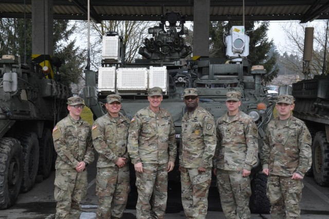 The Field Artillery Squadron, 2d Cavalry Regiment hosts Maj. Gen. Wilson Shoffner, Fires Center of Excellence and Fort Sill commanding general, and Command Sgt. Maj. Carl Fagan, the senior enlisted advisor for the FCoE and Fort Sill, for a firsthand look at Troops training with the new Directed Energy 5kW laser weapon system at the Grafenwoehr Training Area, Germany, Mar. 6, 2018. (From left to right: Sgt. Anthony Devries, 2nd Lt. Arturo Pacheco, Maj. Gen. Wilson Shoffner, Command Sgt. Maj. Carl Fagan, Spc. Zachary Ringling and Spc. Richard Duke)