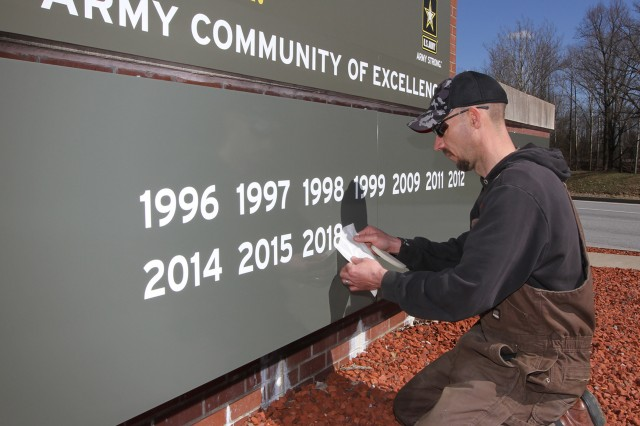 Justin Godsey of the GINN Group adheres the 2018 decal to the Chaffee tank static display at Fort Knox's Chaffee (Main) Gate. The display shows all of the years the post has received ACOE accolades.