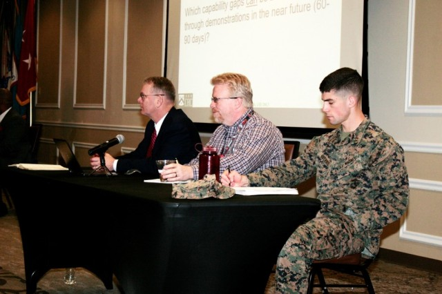 Three members of the Synthetic Training Environment Cross Functional Team, including (from left to right) Robert Munsey, U.S. Army Training and Doctrine Command capability manager, Virtual & Gaming; Mike Barnett, Army Game Studio; and Capt. Pierce Guthrie, U.S. Marine Corps Training and Education Command Marine Air-Ground Task Force Training Simulations Branch, participate in the Soldier/Squad Virtual Trainer Industry Day as panel members during a question and answer session.