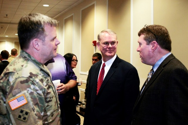 Col. Jay Bullock and Robert Munsey (middle), Synthetic Training Environment Cross Functional Team, talk with industry leaders during a break at the Squad/Soldier Virtual Trainer Industry Day event Feb. 26, 2018. The purpose of the gathering was to develop collaborative efforts between the Army, industry and academia, which will refine requirements and provide possible material solutions for the S/SVT training capability and STE/CFT.