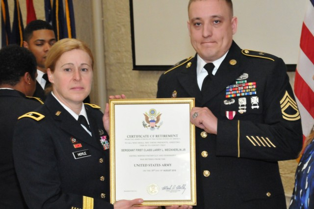 Sgt. 1st Class Larry Weckherlin receives his certificate of retirement from Brig. Gen. Heidi Hoyle during the Rock Island Arsenal Retirement and Retreat Ceremony, March 8. (Photo by: Tony Lopez, JMC Public and Congressional Affairs)