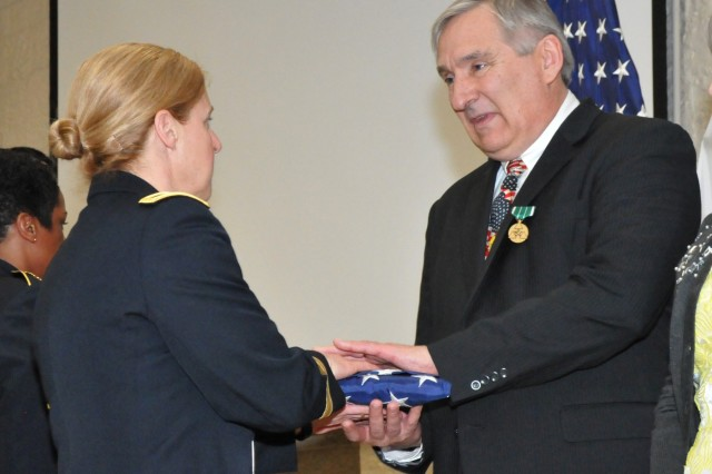 David House receives his U.S. flag from Brig. Gen. Heidi Hoyle during the Rock Island Arsenal Retirement and Retreat Ceremony, March 8. (Photo by: Tony Lopez, JMC Public and Congressional Affairs)