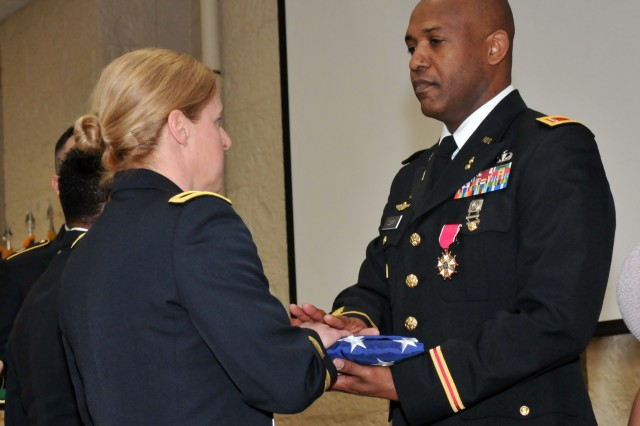 Chief Warrant Officer 5 Alston Cleary receives his U.S. flag from Brig. Gen. Heidi Hoyle during the Rock Island Arsenal Retirement and Retreat Ceremony, March 8. (Photo by: Tony Lopez, JMC Public and Congressional Affairs)