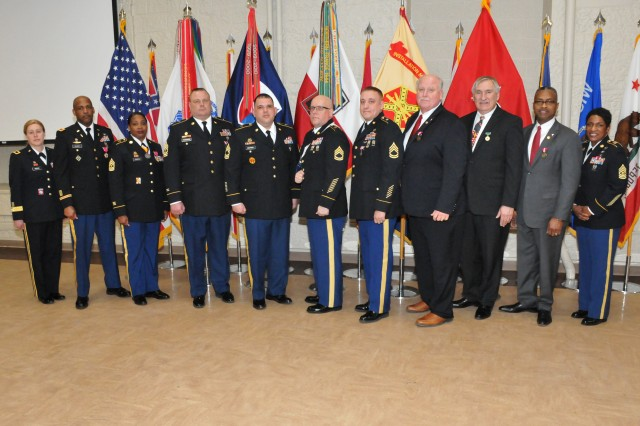 Nine retirees stand for a group photo following the quarterly Rock Island Arsenal Retirement and Retreat Ceremony, March 8. From left to right: Brig. Gen. Heidi Hoyle, commanding general, JMC; retirees: Chief Warrant Officer 5 Alston Cleary, Sgt. Maj. Cherrie Parrish, 1st Sgt. Gary Friedrickson, Master Sgt. William Cintron-Flores, Sgt. 1st Class Dennis Shepard, Sgt. 1st Class Larry Weckherlin, Mark Clark, David House and Rickey Peer; and Command Sgt. Maj. Tomeka O'Neal, JMC. (Photo by: Tony Lopez, JMC Public and Congressional Affairs)