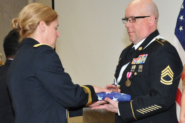 Sgt. 1st Class Dennis Shepard receives his U.S. flag from Brig. Gen. Heidi Hoyle during the Rock Island Arsenal Retirement and Retreat Ceremony, March 8. (Photo by: Tony Lopez, JMC Public and Congressional Affairs)