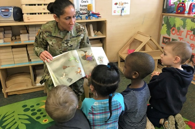 Maj. Maritza Garriga, 7th Mission Support Command, reads to preschoolers March 8 in a classroom at the Vogelweh Child Development Center.