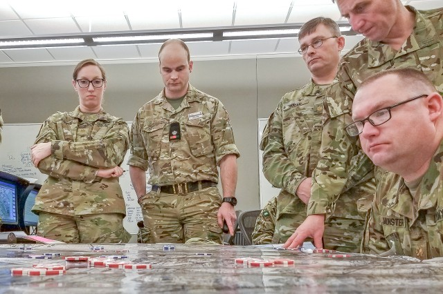 "U.S. officers from CGSC and U.K. officers from the Intermediate Command and Staff College (Land) study the battle map March 7 during Exercise Eagle Owl at the Command and General Staff College, Fort Leavenworth, Kansas. (l-r) Majors Erin Stevens, Will Holloway (U.K.) Doug Hayes, Rich Hunt (U.K.), and Jeff Munster. (Photo by Major Charles ""Sal"" Soliata)"