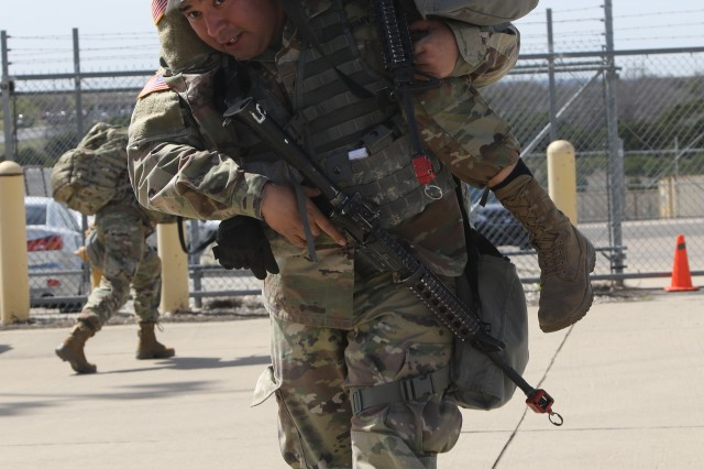 """A soldier performs a fireman's carry to evacuate another soldier on the final leg of the 553rd Combat Sustainment Support Battalion's """"Best Squad Competition"""" on Fort Hood, Texas, March 8. Members of the winning team from 664th Ordnance Company received Army Achievement Medals and four-day passes for their victory."""