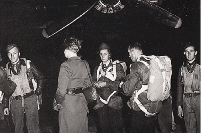 Jedburghs stand in front of a B-24 just before night takeoff at Area T, Harrington Airdrome, England, circa 1944.