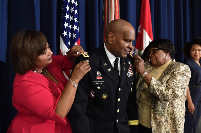 Lt. Gen. Leslie C. Smith, center, stands as his wife, Vanedra, and his mother, Lily, affix new rank epaulets to his jacket during a promotion ceremony held Feb. 9 at Fort McNair in Washington. Smith was promoted two days after being sworn in as the Army's 66th inspector general.