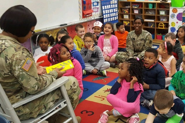 80th Training Command Soldier Master Sgt. Nekia Haywood (in rocking chair) reads to children at Hopkins Elementary School in Chesterfield, Virginia, March 2, 2018, in celebration of Dr. Seuss' birthday.  The famous children's author is honored annually as part of the Read Across America program, an initiative on reading that was created by the National Education Association.  Sitting on the floor with the children is Sgt. 1st Class Lavett Miller, with the 80th TC. (Photo by Mrs. Fran Mitchell, 80th TC Family Programs)