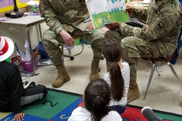 (Right) Brig. Gen. Fletcher Washington, deputy commanding general of the 80th Training Command, reads to children at Hopkins Elementary School in Chesterfield, Virginia, on March 2, 2018, in celebration of Dr. Seuss' birthday. (Left) Lt. Col. Jason Logan, 80th TC chaplain, enjoys the children's reactions to the story. Dr. Seuss' birthday is honored annually as part of the Read Across America program, an initiative on reading that was created by the National Education Association. 80th Training Command Soldiers volunteered their time to visit and read to school children to celebrate the nationwide event.