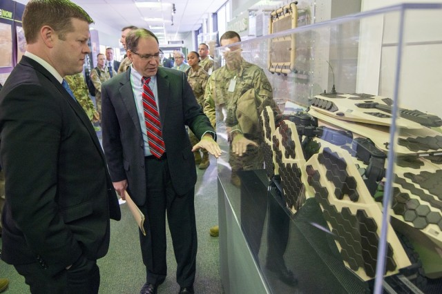Dr. Paul D. Rogers, center, director of the U.S. Army Tank Automotive Research, Development and Engineering Center (TARDEC), shows Undersecretary of the Army Ryan D. McCarthy a combat vehicle design from a Soldier Innovation Workshop during a Jan. 18 tour of TARDEC. The workshop brings together the industrial design skills of students from Detroit's College for Creative Studies and the battlefield experience of Soldiers to develop innovative approaches to Army projects.
