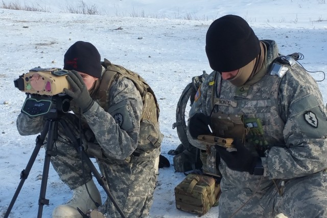 Pfc. Anthony Greenwood (left) finds a target in his area using the Joint Effects Targeting System Target Laser Designation System (JETS TLDS), while Pfc. Montiel of utilizes Precision Fires-Dismounted (PF-D) to send a fire mission to higher headquarters. Both Soldiers are from Battery D, 2nd Battalion, 8th Field Artillery Regiment, taking part in an operational test of JETS TLDS at the Fox Den Observation Post in the Texas Training Area at the Cold Regions Test Center, Fort Greely.