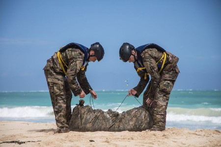 Soldiers with the 25th Infantry Division take apart their poncho raft after a helocast swim on Bellows Air Force Station, Hawaii, March 1, 2018. In preparation for the 2018 Best Ranger Competition, the 25th Infantry Division Best Ranger Competition teams construct a poncho raft containing their rucksacks and M4 rifles before helocasting out of a Bell UH-1 Iroquois helicopter.