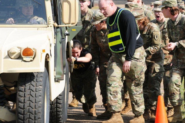 Pvt. Rebecca Sarmiento, A Co. 1-13th Avn. Regt., takes part in the 25-meter Humvee push with her team during the AIT Warrior Challenge March 10.