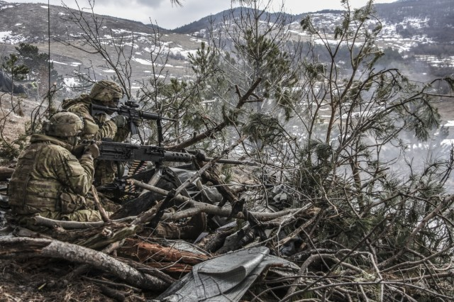 The muzzle blast from a M2 .50 caliber machine gun tears through the camouflage as gunners from the 173rd Airborne Brigade Support Battalion conduct base defense live fire training this week in Postojna, Slovenia.