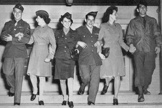 Soldiers and WACs walk down some stairs arm-in-arm during a 1945 event.