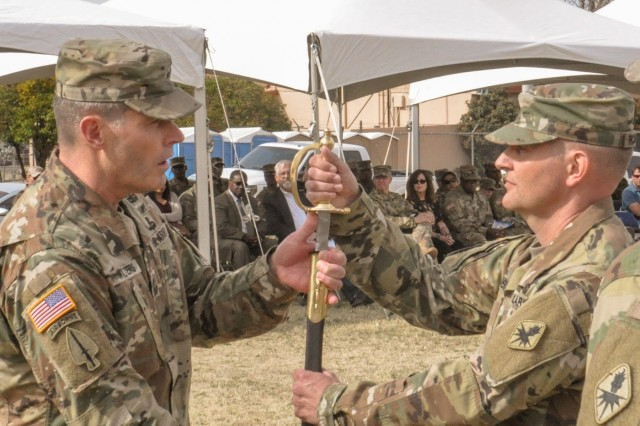 Maj. Gen. Robert P. Walters Jr., Commanding General of the U.S. Army Intelligence Center of Excellence and Fort Huachuca, passes an NCO Sword to Command Sgt. Maj. Warren K. Robinson during the Change of Responsibility ceremony at Brown Parade Field March 16. (Photo by Sfc. Luis Pascual)