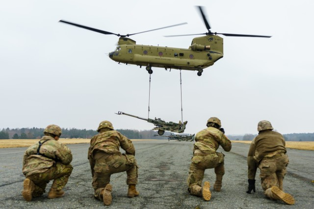 A CH-47 Chinook helicopter crew assigned to Company B, 2nd General Support Aviation Battalion, 227th Aviation Regiment, 1st Combat Aviation Brigade, 1st Cavalry Division, lifts an M777 howitzer as cannon crewmembers with Battery B, Field Artillery Squadron, 2nd Cavalry Regiment, observe at an airfield near Grafenwoehr, Germany Mar. 6, 2018.