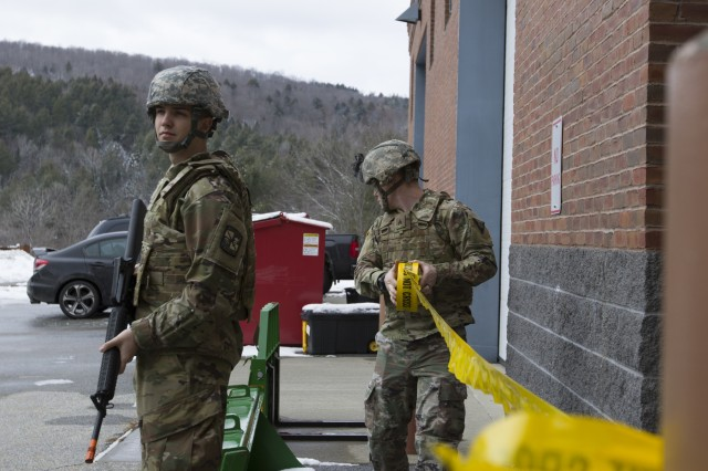 U.S. Army Cadet Bradley Thomas, left, Norwich University, provides security, while Sgt. Jay Atherton, a team leader, 172nd Law Enforcement Detachment, Garrison Support Command, Vermont National Guard, cordons off the area during a simulated active shooter scenario at the Vermont National Guard Readiness and Regional Technology Center in Northfield, Vt., March 3, 2018. The 172nd LED completed a culminating exercise that used several scenarios to address their new focus on law enforcement since reorganizing from a combative role.