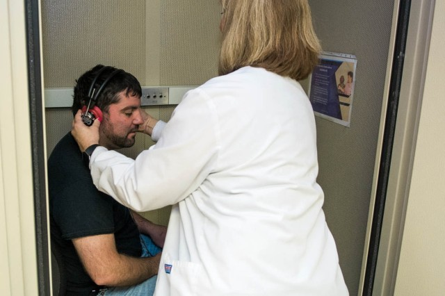 Debra Generose, registered nurse, adjusts a headset for an employee participating in an audiogram hearing test at Tobyhanna Army Depot.