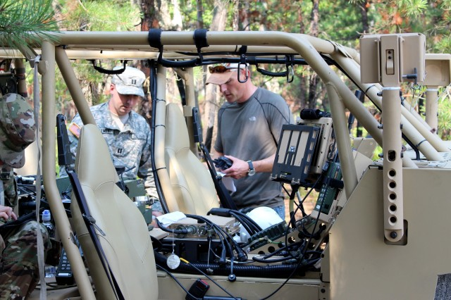 R.J. Regars, CERDEC engineer, reviews exercise operations orders in July with Capt. Ezra McCalment, U.S. Army Reserve network engineer based at Fort Belvoir, Virginia, during the Expeditionary Command Post Science and Technology Field-Based Risk Reduction Exercise at Fort Dix. The exercise incorporated the Ultralight Command Post prototype shown here. The prototype is a fully integrated mobile command post mounted on a Polaris DAGOR vehicle that is designed to serve as a forward operating command node for specialized missions such as air assault, airborne and other initial entry operations.