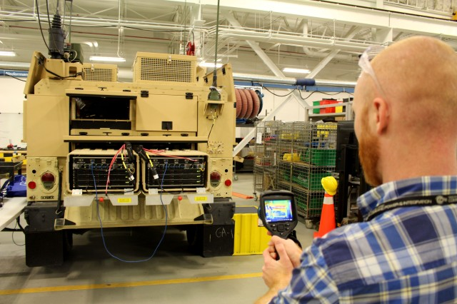 CERDEC's Expeditionary Command Post Capability project personnel are putting the finishing touches on the Command Post Platform -- Improved demonstrator, an on-the-move capability that supports an entire brigade's server needs. Engineers collaborated with industry to design and test a novel cooling solution that would allow the servers to operate from inside the vehicle. Using a thermal imaging camera, Kyle Swisher, CERDEC engineer, measures the servers' heat output on Dec. 6 to identify hot spots and assess cooling efficiency at CERDEC's C4ISR Prototype Integration Facility, Aberdeen Proving Ground, Maryland.